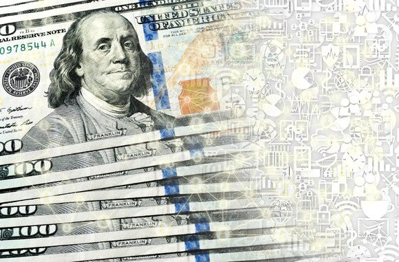 A small fanned stack of hundred dollar bills being transformed into digital currency.