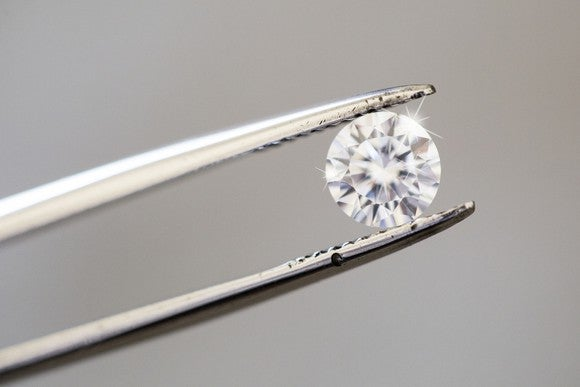 A round diamond being held by tweezers.