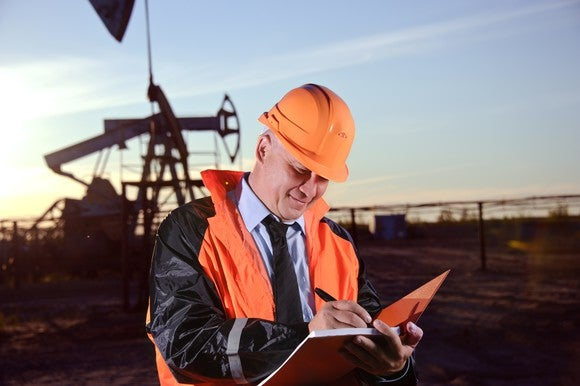 A man standing in front of an oil well in an orange-and-black jacket and orange hard hat while writing in a notebook