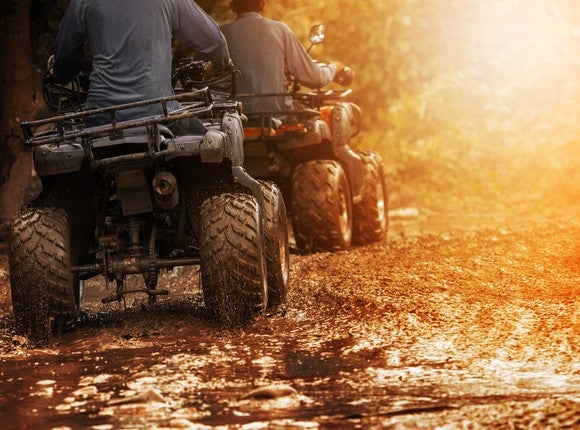 Two people riding ATVs through the mud.