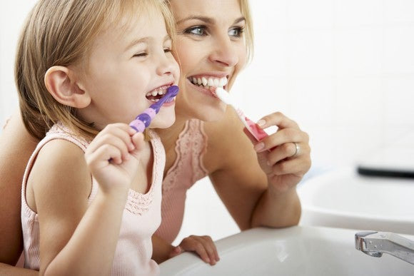 A mother and daughter brushing their teeth.