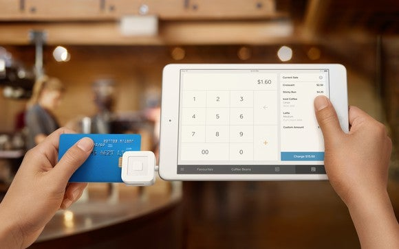 A Square chip reader connected to a tablet held by hands swiping a credit card.