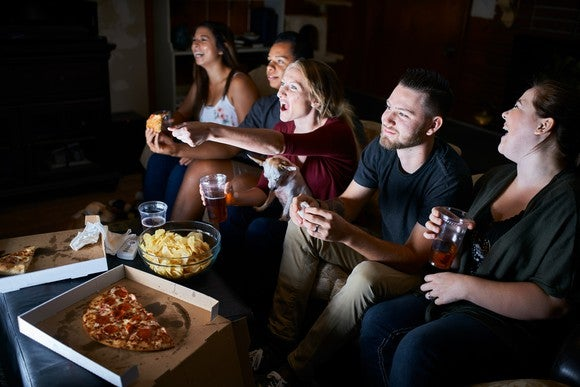 Friends watching TV and eating pizza.
