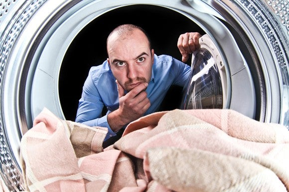 Man staring into a washing machine and pondering, seen from inside the machine's drum