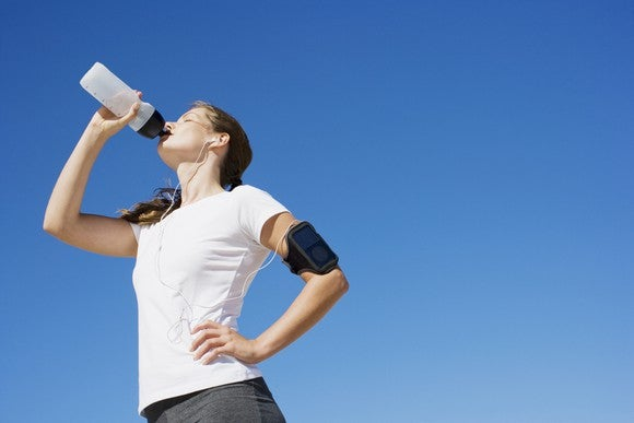 A jogger drinks out of a sports bottle.