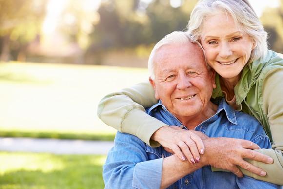 Senior woman with arms around senior man