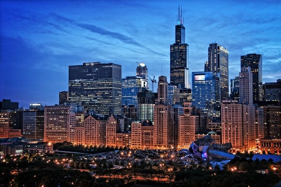 Chicago skyline from Millennium Park, including the Willis Tower and other Loop buildings under a twilight sky with cirrus clouds.