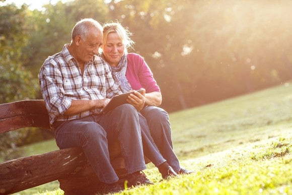 Senior couple using a tablet outdoors