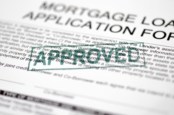 Mortgage loan application with approved stamped on top.