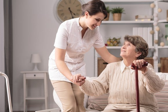 Assisted living center caregiver helping an elderly person to her feet.