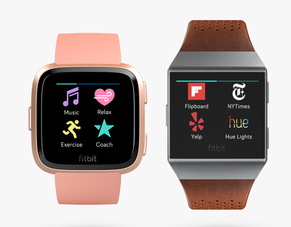 The Versa on the left and Ionic on the right. Versa is slightly smaller and has rounded corners, displayed in pink. The Ionic is in gray and has a brown leather wristband.