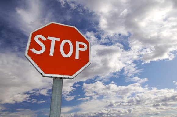 A stop sign surrounded by a partly cloudy sky.