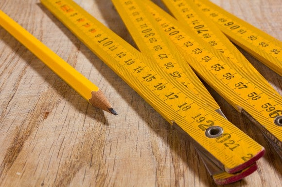 A long yellow measuring stick and yellow pencil side by side on a wooden table.