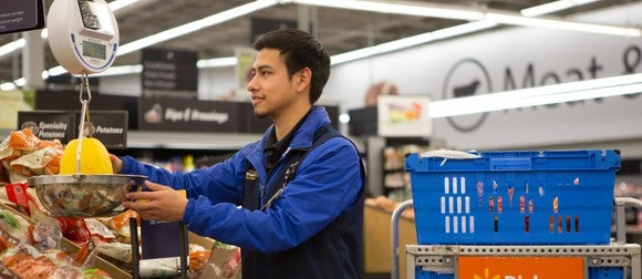 A Walmart employee weighs on item on a scale.