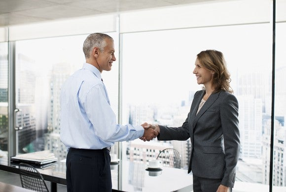 Professional older man shaking hands with a woman in a business suit
