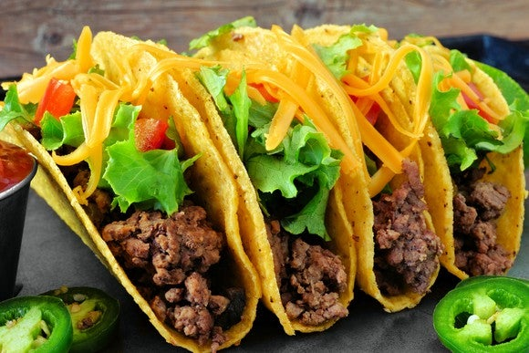 Four crispy corn shell tacos with lettuce, cheese, tomatoes, and jalapeno slices