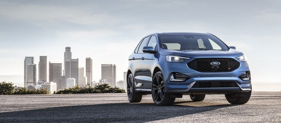 A blue 2019 Ford Edge ST, a midsize high performance SUV, is shown parked with a city skyline in the background.
