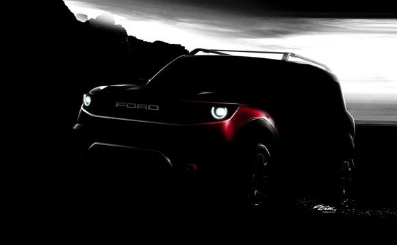 A darkened photo showing a small Ford SUV parked on a rocky grade.