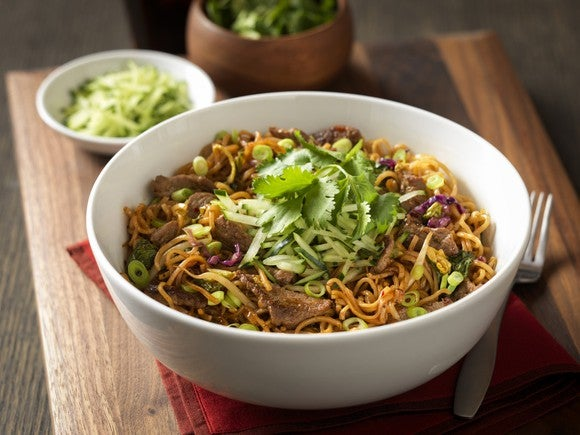 White bowl of noodles and beef with scallions and other ingredients, on a wood table with a bowl of salad and another side dish.