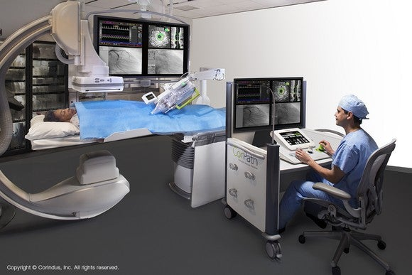 A seated physician in scrubs using the CorPath GRX System with a patient lying under it