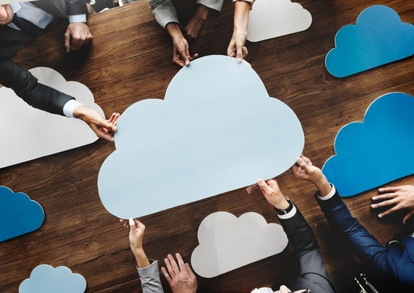 Business team holding cutouts of clouds in office; symbolic cloud computing meeting.