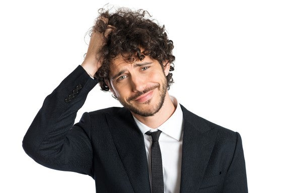 A confused, lightly bearded young man in a suit scratching the top of his curly hair.