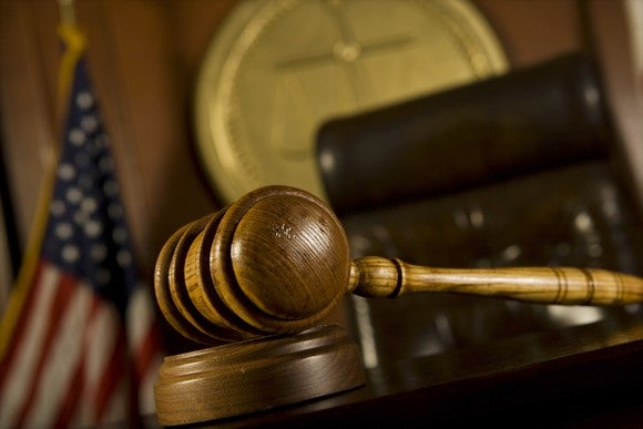 A courtroom, with a judge's gavel, chair, and seal visible.