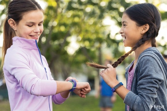 Two girls wears Fitbit Ace smartwatches