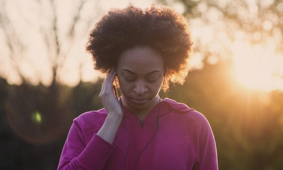 A woman listening on headphones outdoors at sunrise.
