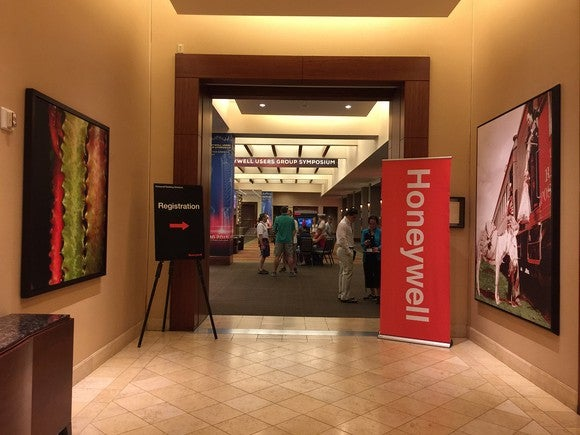 Antechamber of a Honeywell conference with artwork and the Honeywell logo with a sign pointing to registration.