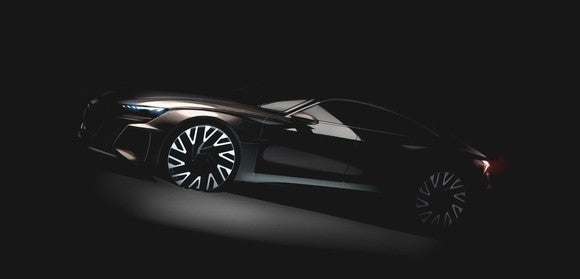 The prototype Audi e-tron GT, a low-slung four-door shown in shadows.