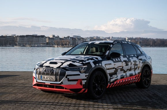 Audi's e-tron prototype, a luxury SUV wrapped in vividly-patterned camouflage, parked on the shore of Lake Geneva.