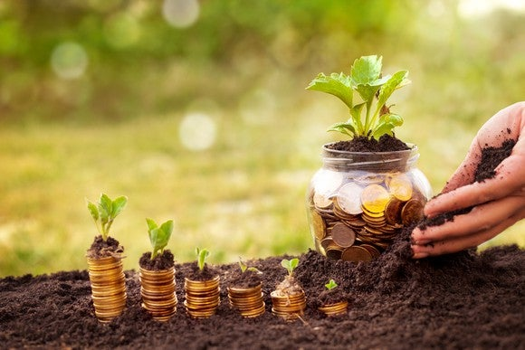 A hand planting a jar of coins next to rising stacks of coins with plants on top.