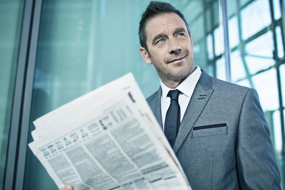 A smirking man in a suit reading a financial newspaper.