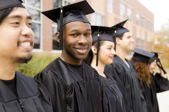 Row of smiling young adults in black graduation robes and hats standing outside.