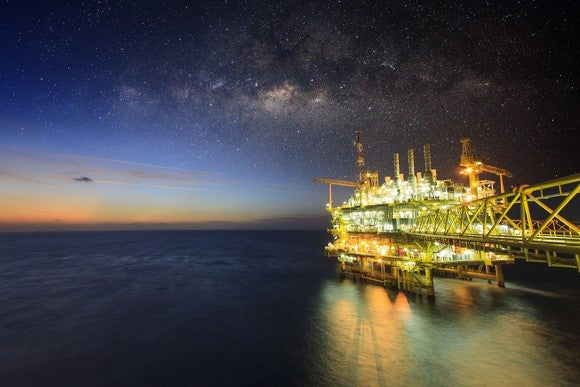 An offshore oil platform with its lights on beneath a half-lit sky