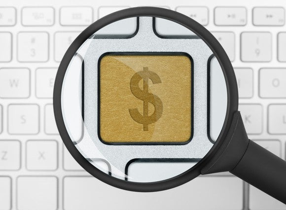 A magnifying glass over a white computer keyboard enlarging a single gold key with a dollar sign on it.