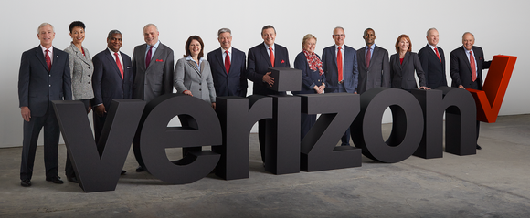 13 people standing behind a 3D representation of the Verizon logo.
