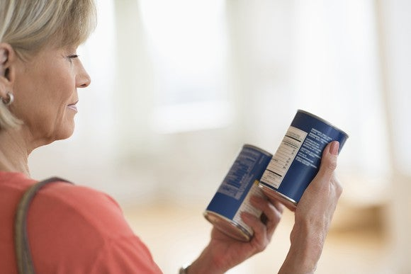 A woman comparing two cans of soup