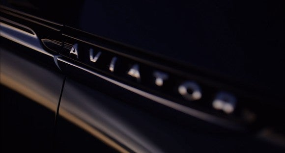 "A teaser image on a vehicle exterior showing ""Aviator""."
