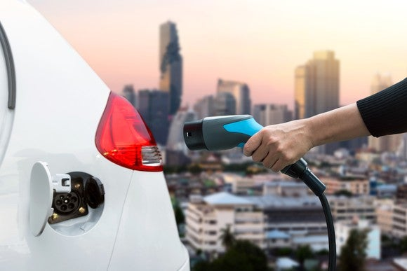 Person's hand holding an EV charger and about to charge (or just finished charging) his or her white vehicle. A city in background.