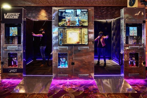 Two people gaming in side-by-side Virtual Zone booths from IGT in a casino.