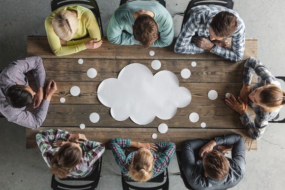 A group of workers sit around a cutout of a cloud.