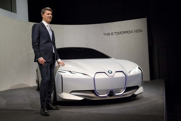 CEO Harald Krueger standing next to a low-slung white sedan, the BMW Vision Dynamics show car.