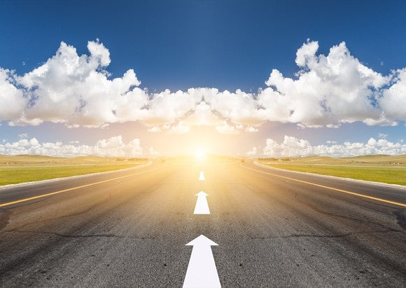 A road with arrows pointing forward towards a bright sun.