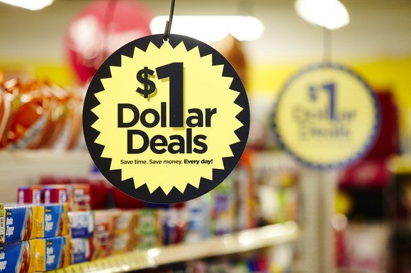 "Close-up of hanging sign labeled ""$1 Dollar Deals"" in Dollar General store aisle."
