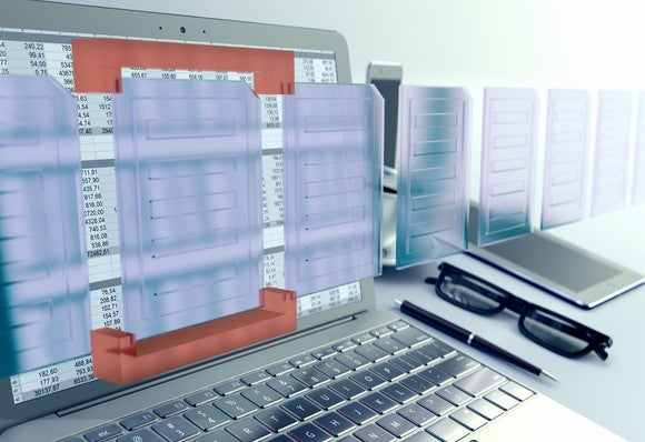 Computer showing spreadsheet numbers, with glasses and pen next to it.