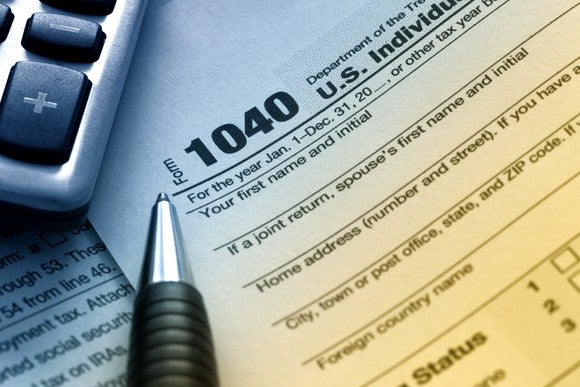 IRS tax form 1040 next to a pen and calculator.