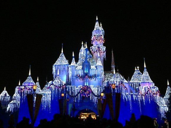 Disneyland castle lit up at night during the winter.