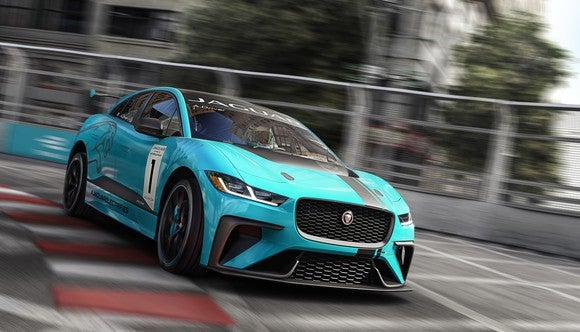 A bright blue Jaguar I-Pace, an electric SUV, is shown on a racing track.
